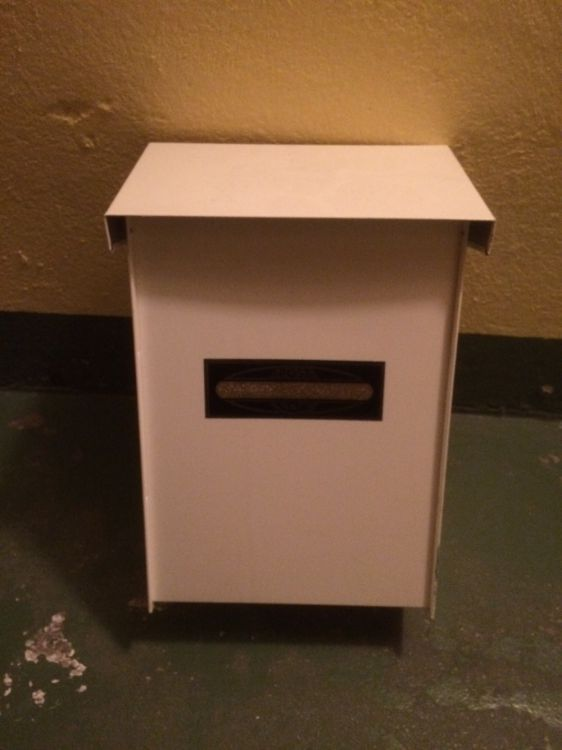 Vita plåtbrevlådor med fin svart/guld postlogga på framsidan