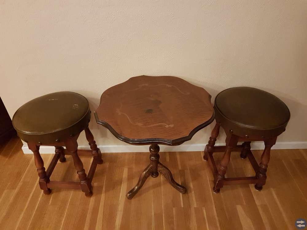 2finna trä pallar med skinnsitts och ett runt bord