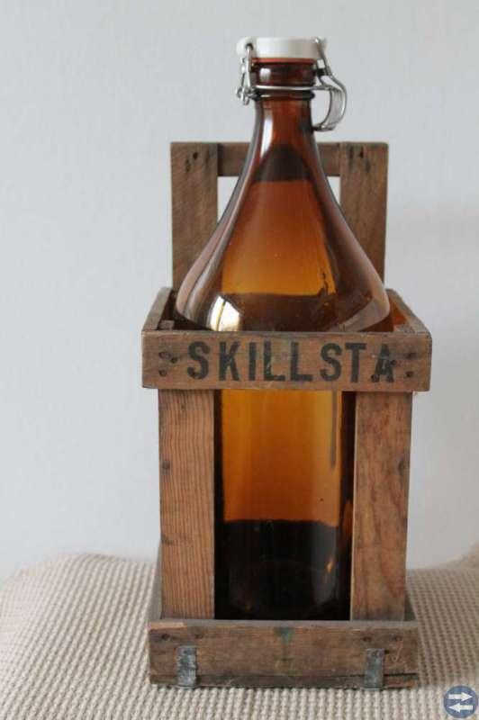 Glasflaska i träställning från Skillsta bryggeri