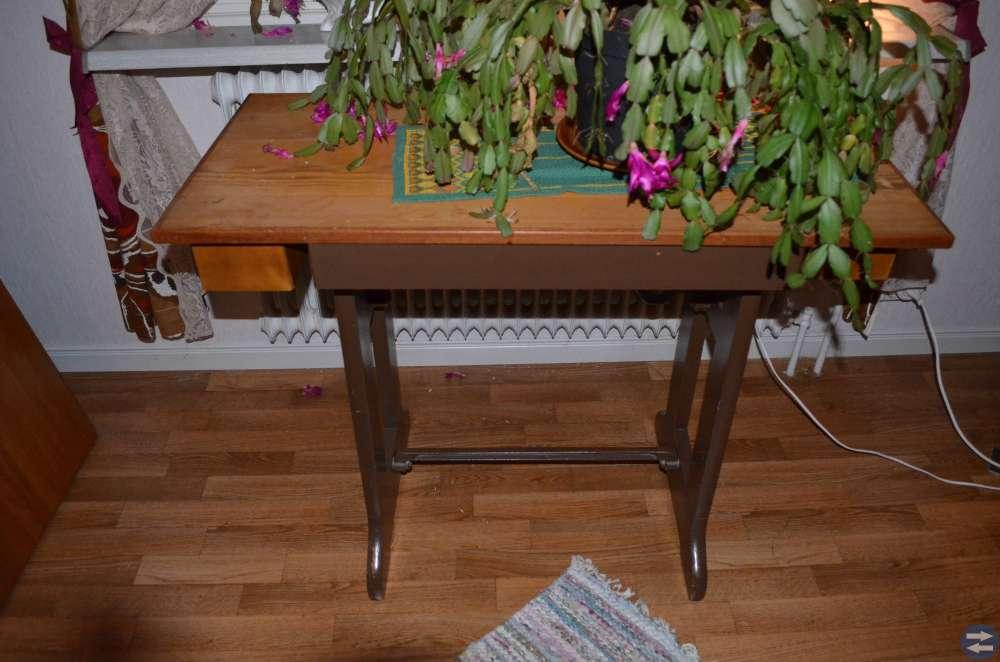 Gammalt symaskinsbord som används som bord