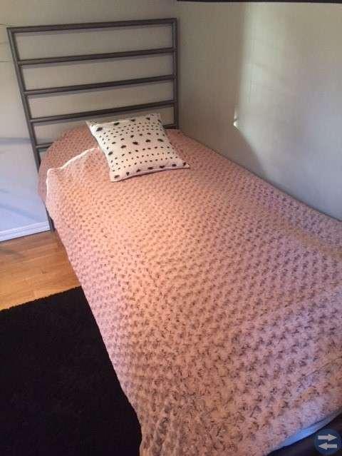 Säng med fräsch madrass, sängbord