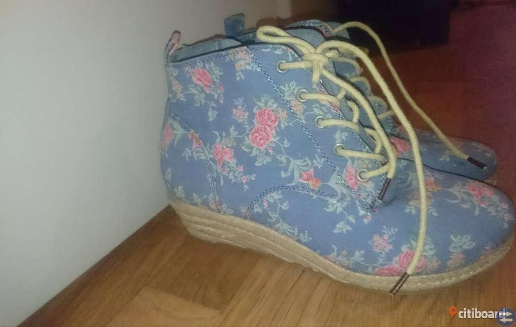 Blå skor med blommor på.